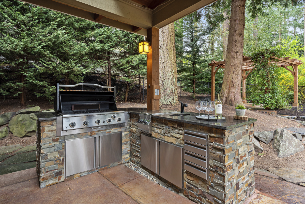 An outdoor barbecue in a wooded back yard.
