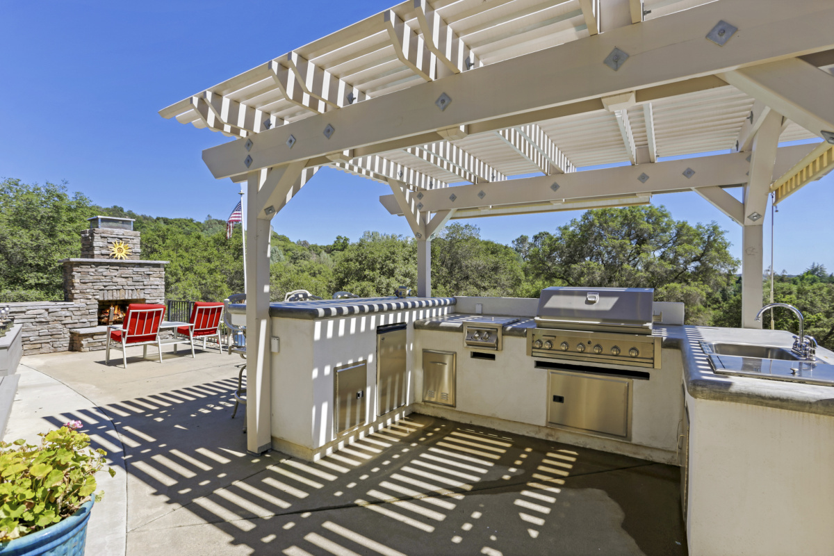 An outdoor barbecue grill with pergola on a sunny day.
