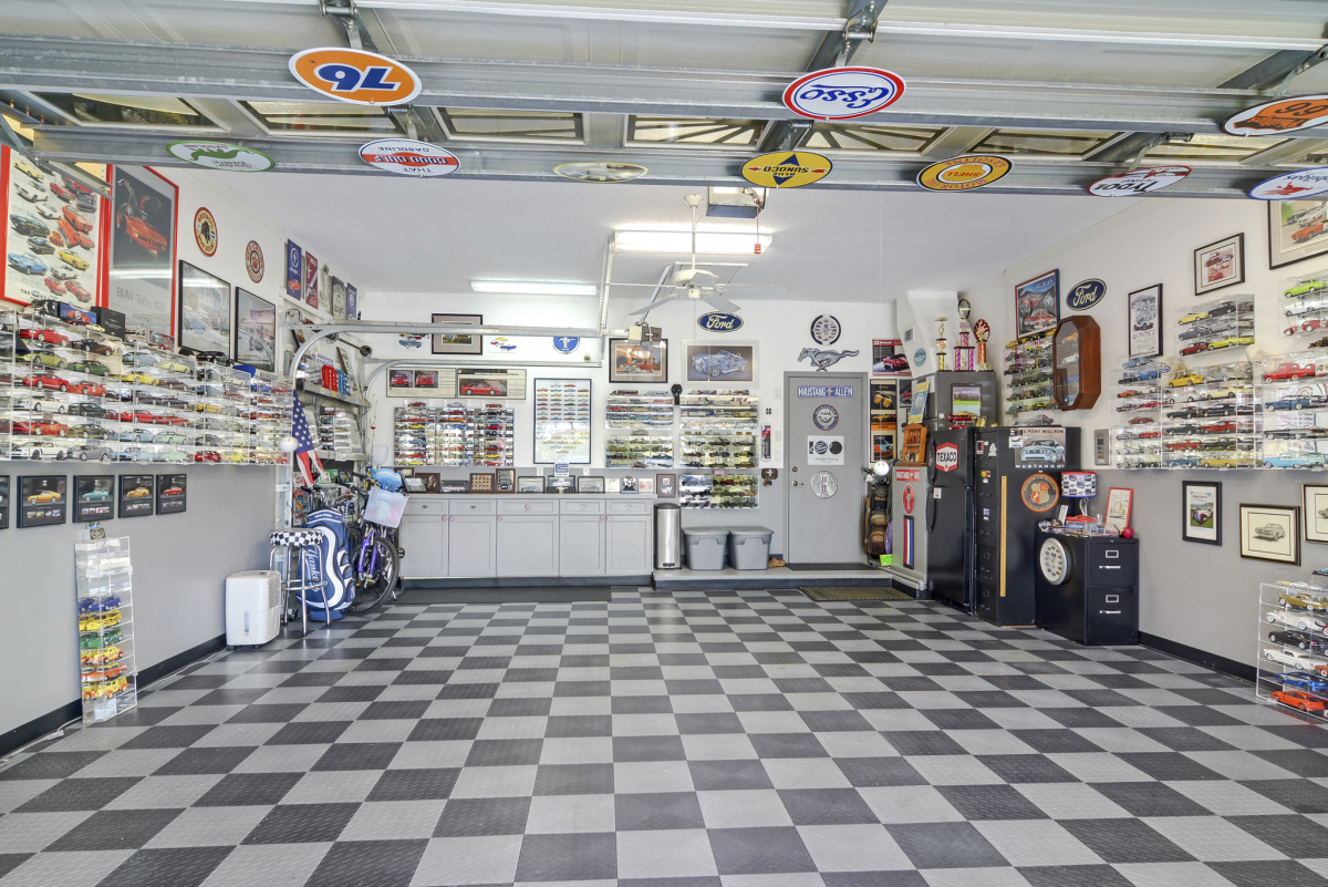 Garage with vintage license plates and checkerboard floor.