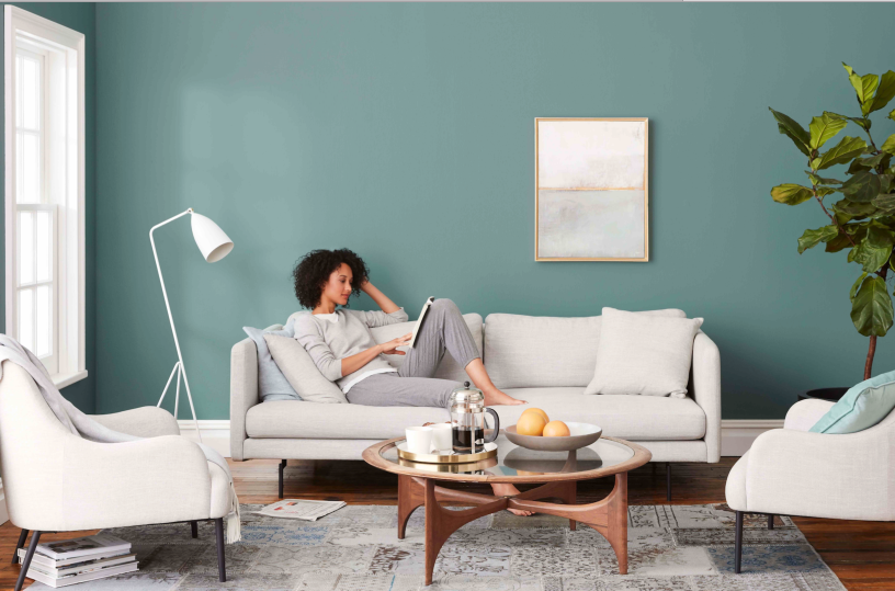 a woman sitting in a living room with a teal wall