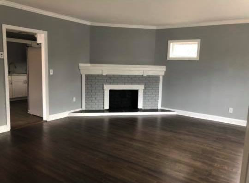 an empty living room with a fireplace