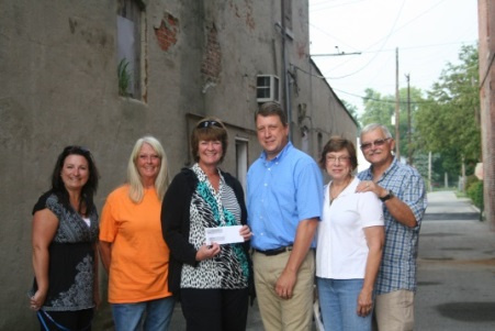 MIBOR President Kathy Hall presents the grant check to members of the Fortville Action, Inc. in the alley.