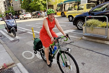 A woman in a red dress riding a bycicle on a bike path