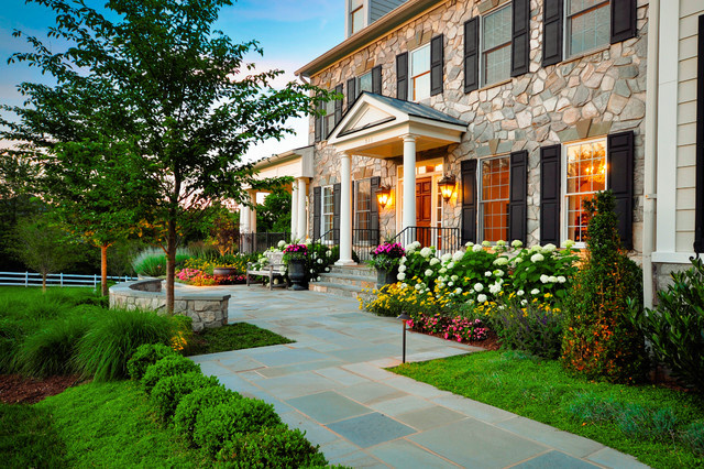 A stone facade house with columned porch and tile walk way.