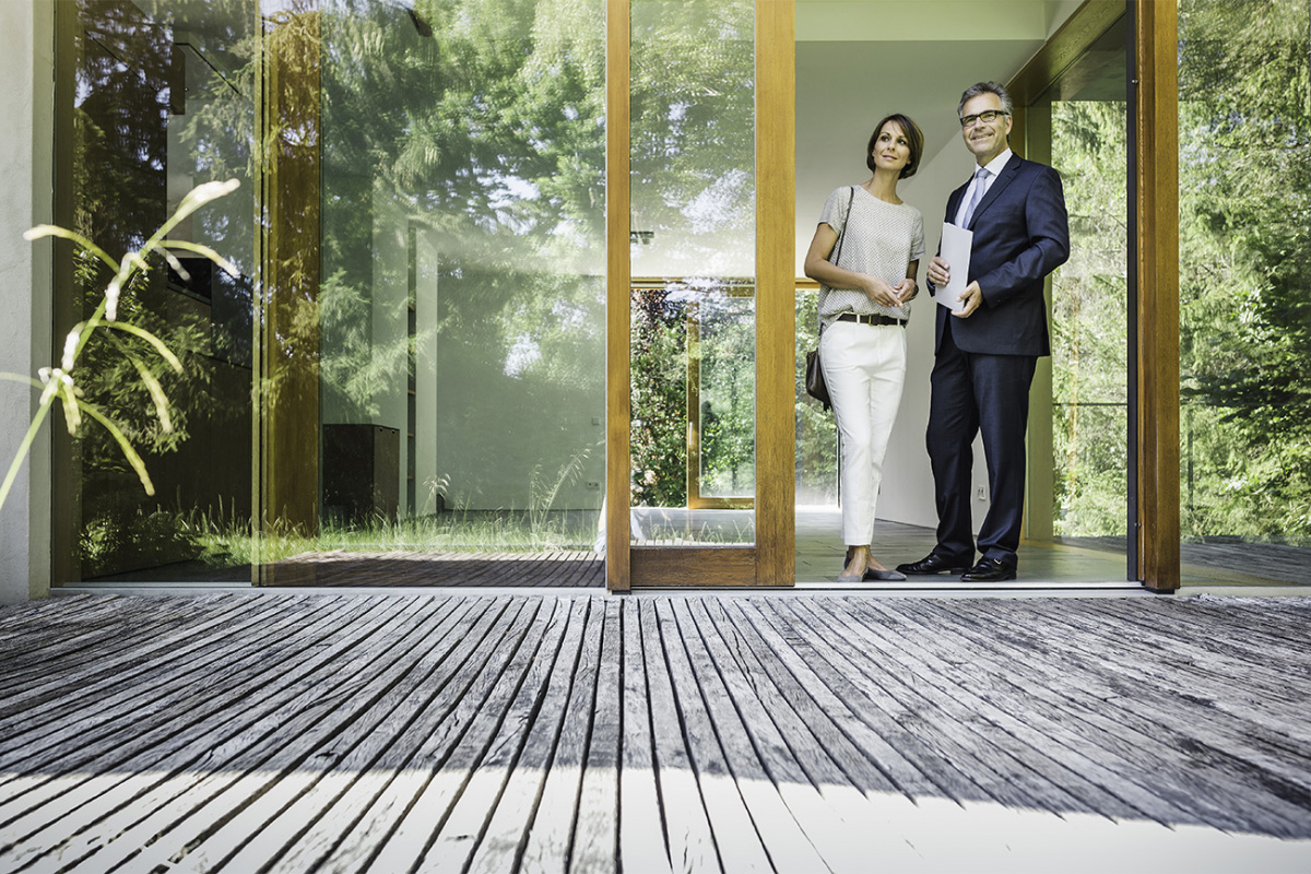Man and woman in the doorway of a house, looking out at a deck