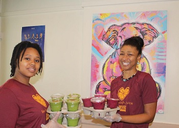 Cups of Goodness juice bar employees carrying trays of fresh juice