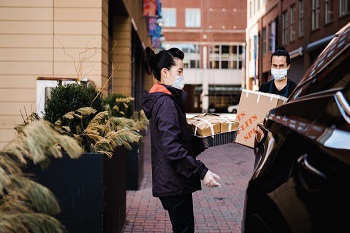 Woman and man wearing masks and gloves carrying a tray of food and a box practicing safe delivery