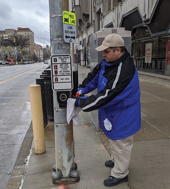 Oakland BID disinfecting the main street crossing signal buttons