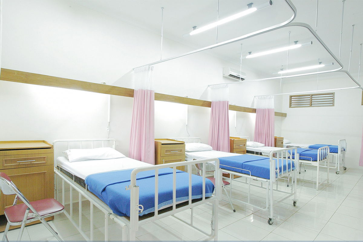 Row of hospital beds and curtains