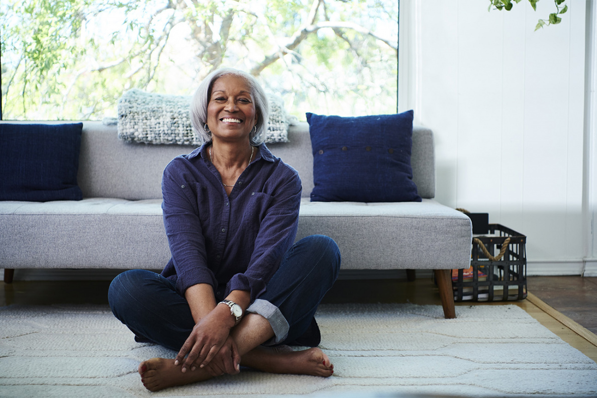 Smiling woman seated cross-legged on living room floor