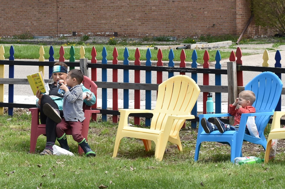 Lansing, MI, Pop-Up Park - a woman sitting on a read chair reading a book to a kid, another kid sitting on a blue chair