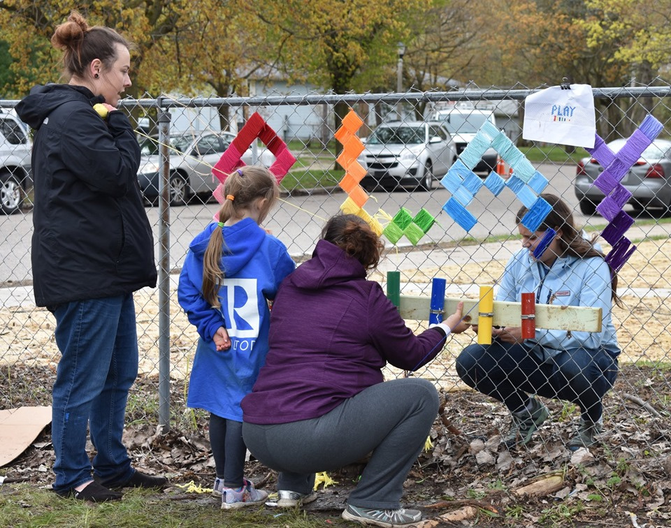 Lansing, MI, Pop-Up Park -girl in blue realtor jacket helping 3 women decorate the park fence