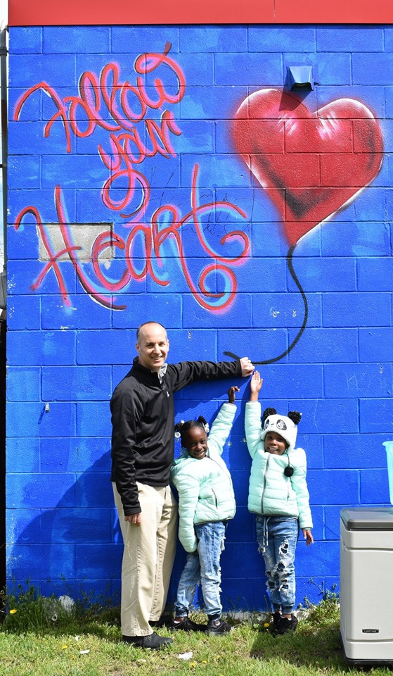 Lansing, MI, Pop-Up Park - man with kids standing in front of a blue wall with a printed message saying follow your heart.