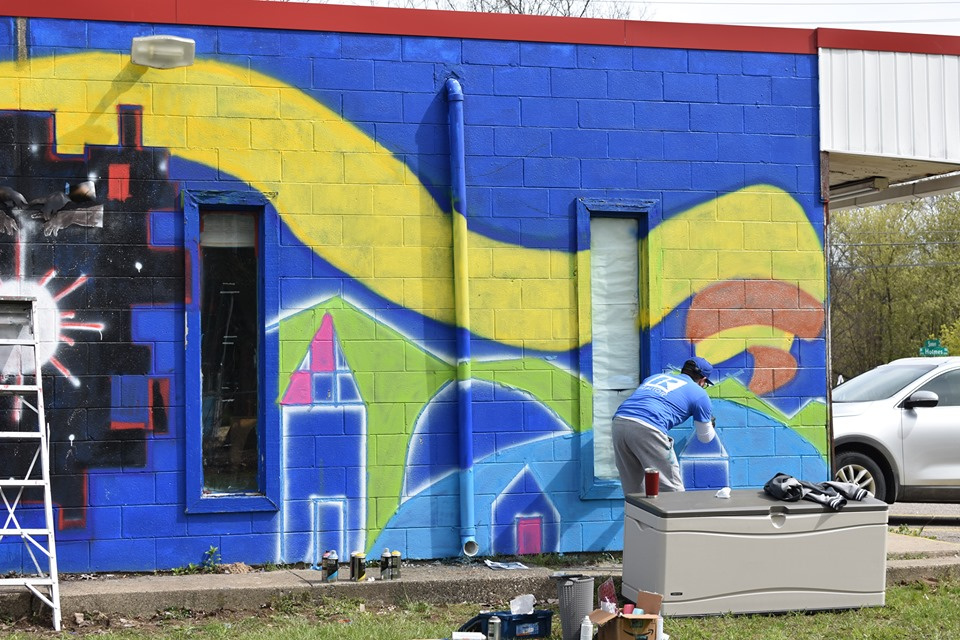 Lansing, MI, Pop-Up Park - REALTOR and talented artist Frank Vicente painting a mural on the back of the building