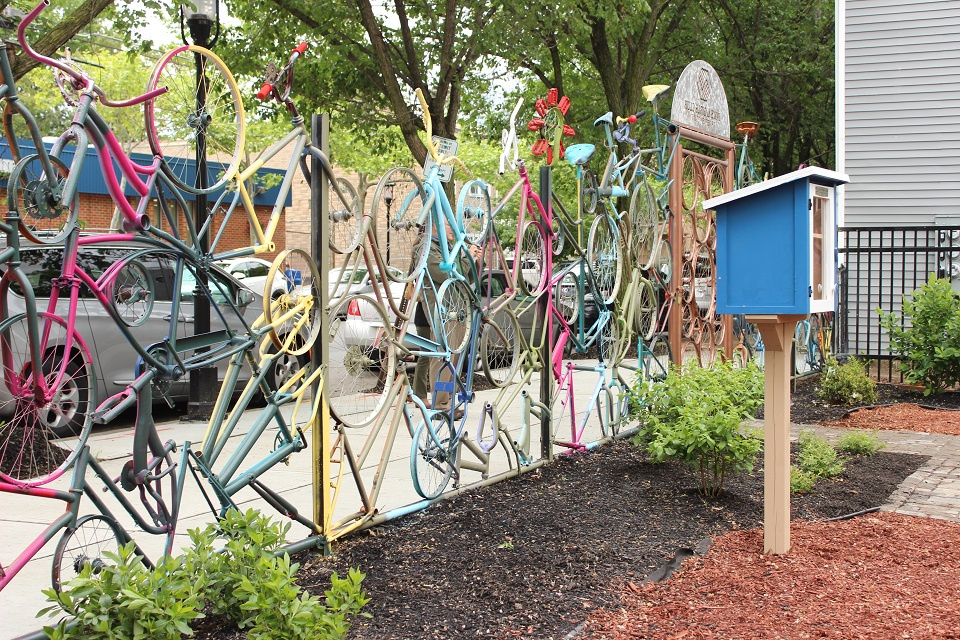 A fence made of colorful bicycle parts with the little library featured in the background.