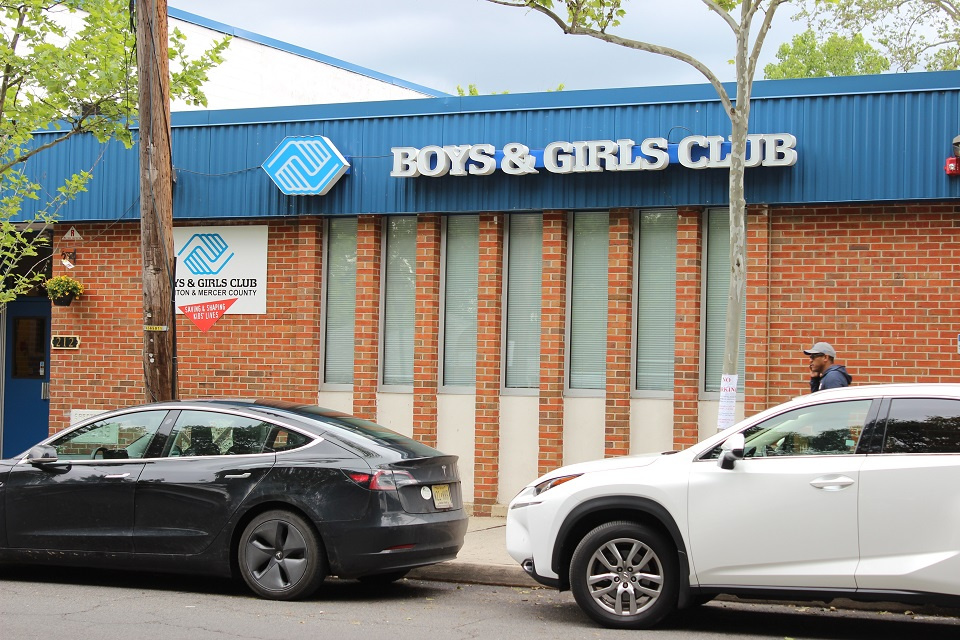 A black and a white car parked right outside the Boys & Girls Club building.