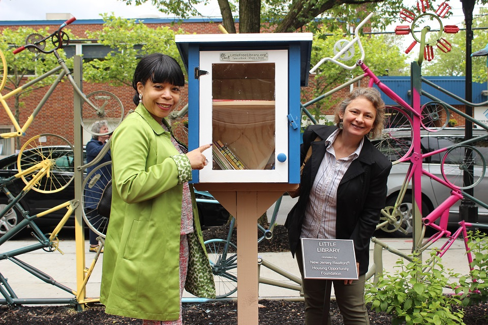 Two women standing right next to the little library and a plaque stating the little library was donated by the NJ REALTORS.