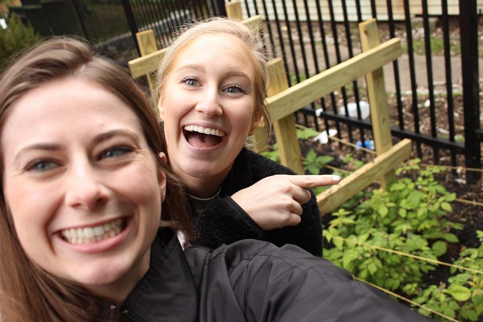 A selfie featuring two women smiling pointing to a gardening bed in the back.