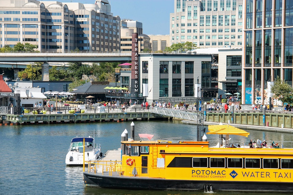 A view of The Wharf showing the Potomac Water Taxi boat and the boardwalk and restaurants in the background