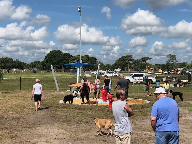 Melbourne, FL dog park - people standing next to painted fire hydrants, covered bench in the background
