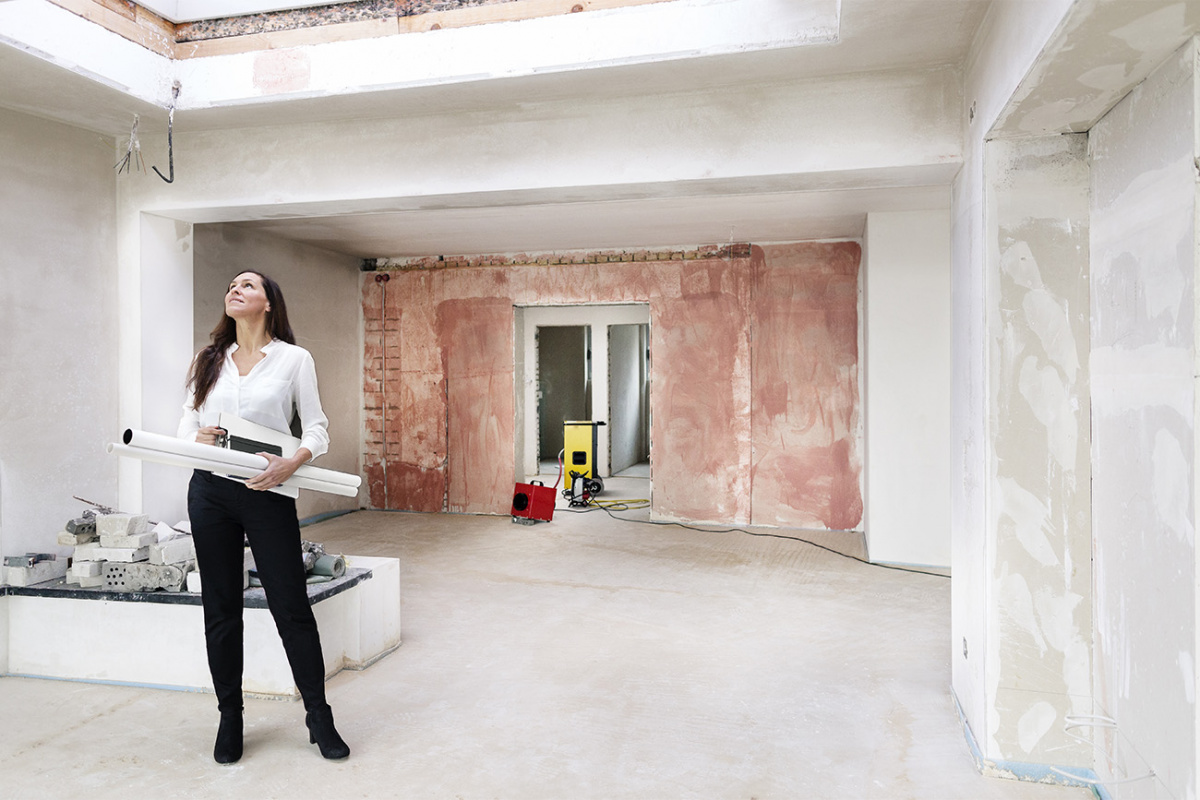 Woman holding blueprints in a home that's being remodeled