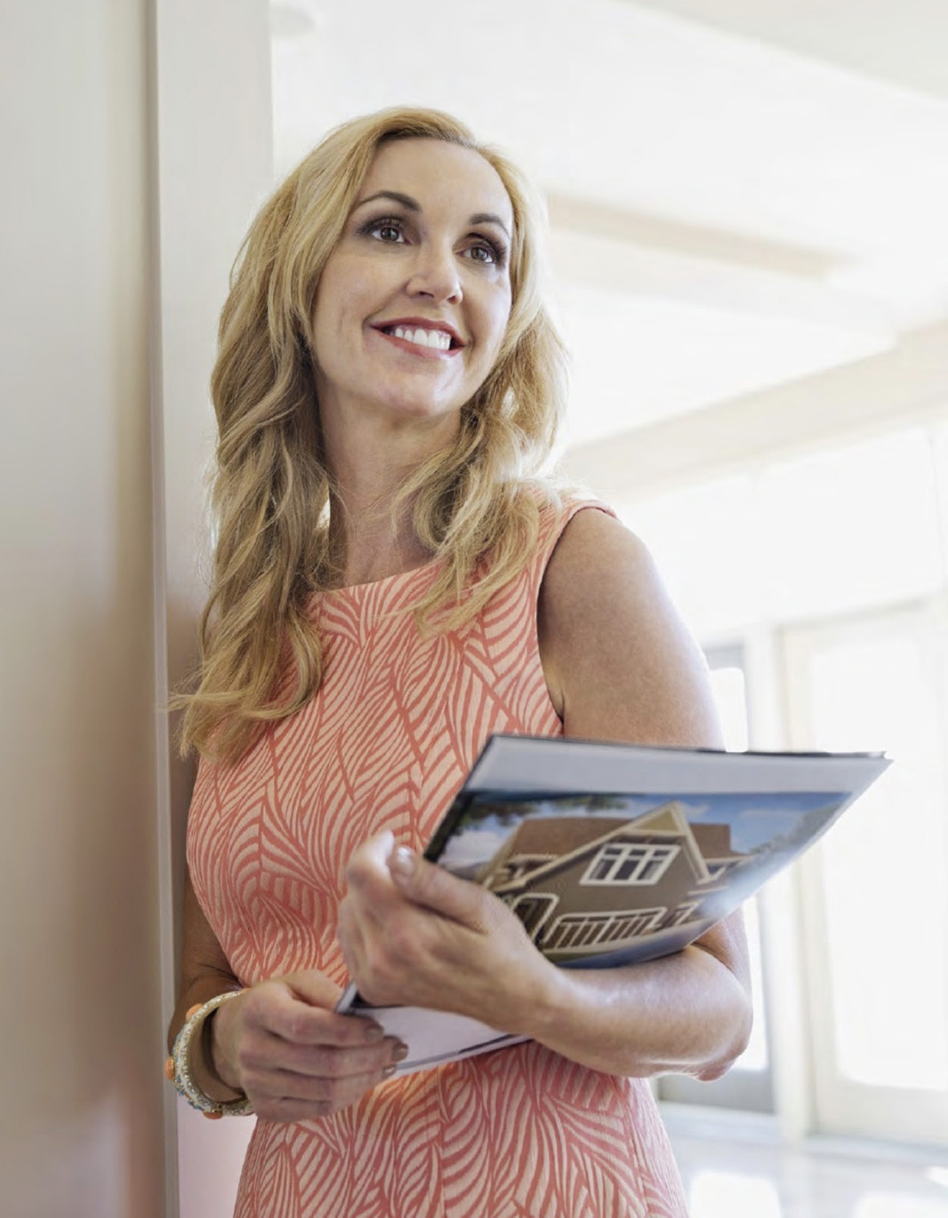 Woman holding real estate brochure