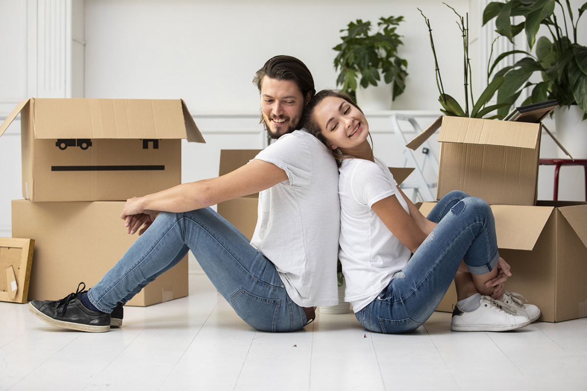 Young couple sitting on the floor with boxes