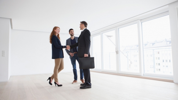 Real estate agent with couple in condo