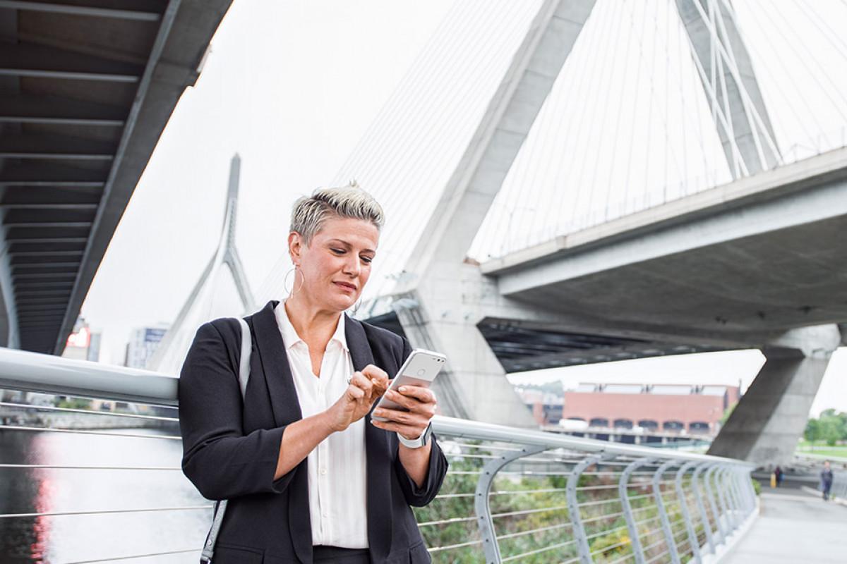 Woman Checking Phone by Bridge
