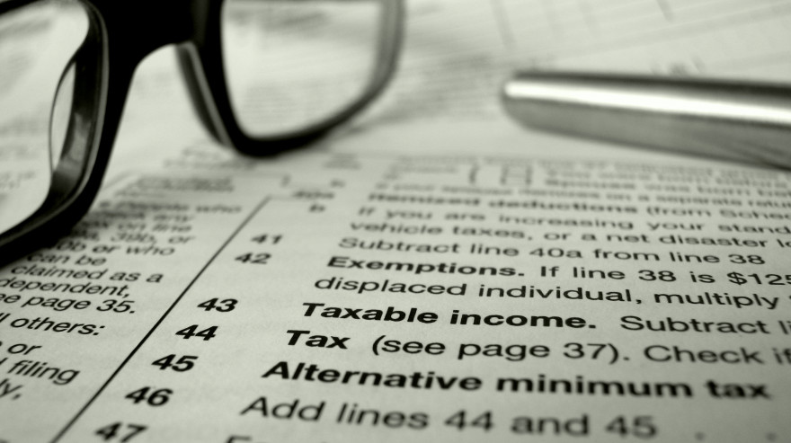 glasses and pen on tax forms