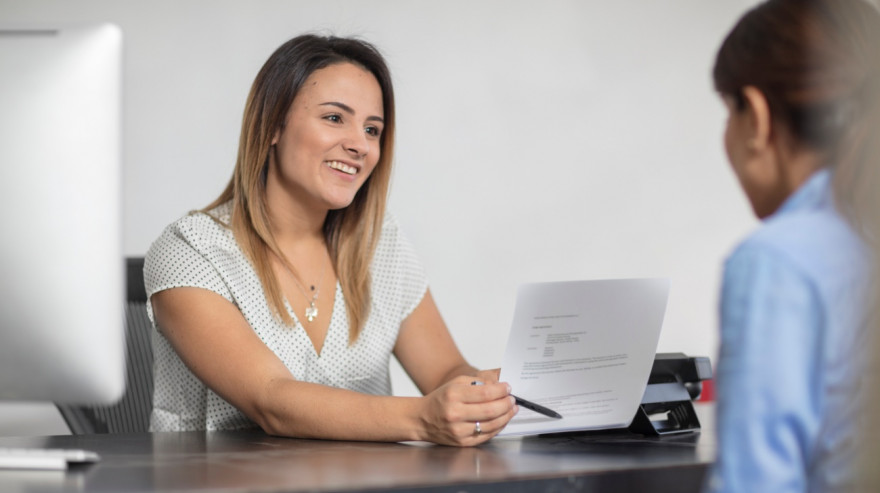 Smiling woman showing contract to client at desk