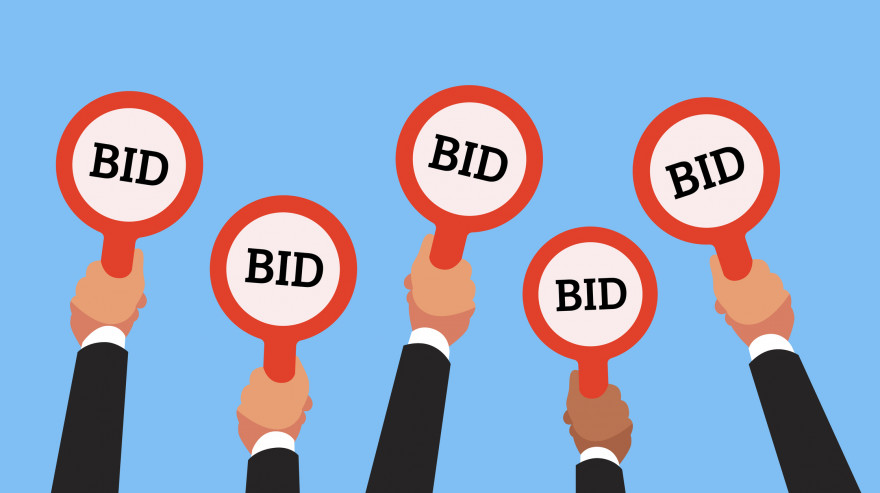 Buyers hands raising auction bid paddles