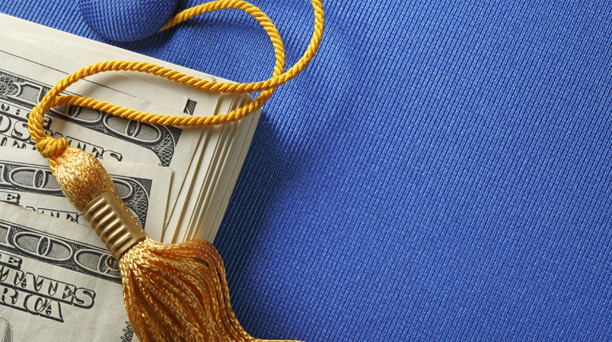Blue mortarboard cap with gold tassel on hundred dollar bills