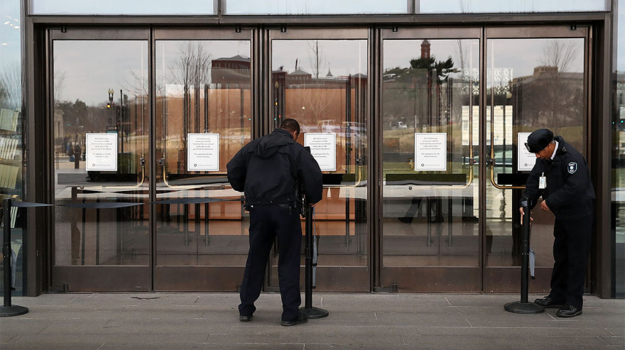 Guards placing barriers in front of museum doors