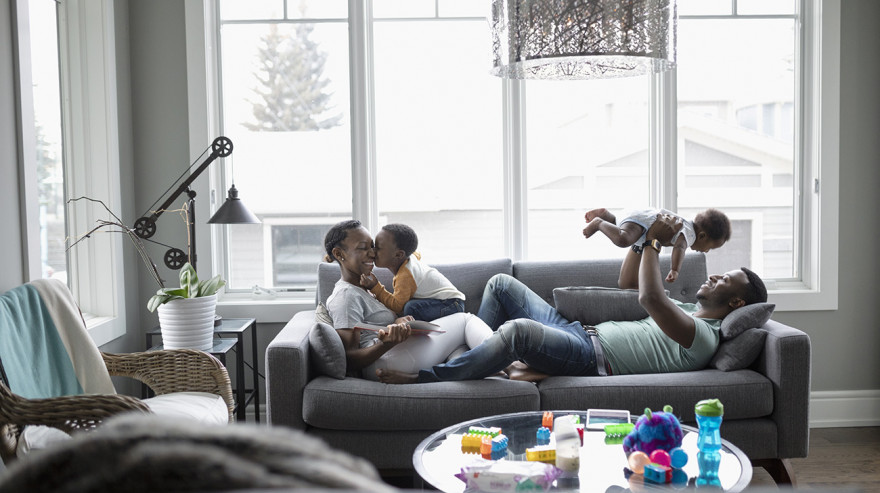 Parents holding children on a couch in a living room