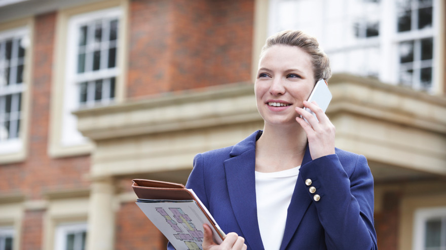 Real Estate Agent Holding Floor Plans While on the Phone
