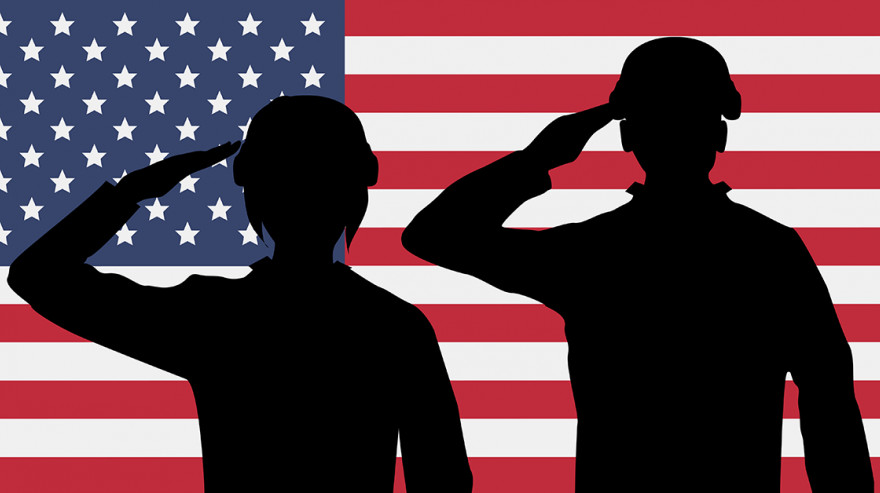 Silhouette of military personnel against U.S. flag