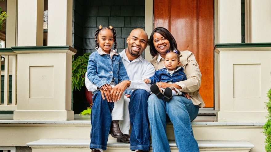 Family of 4 sitting on the porch of their home, smiling