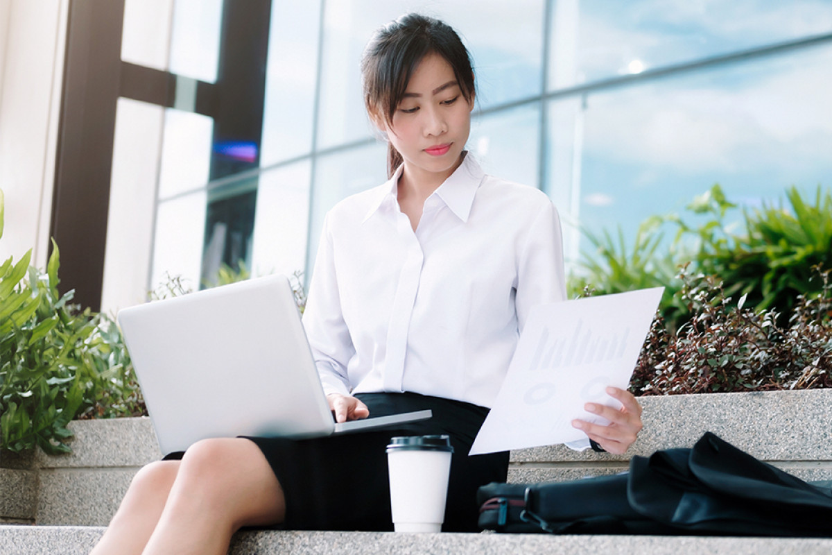 Young professional woman on steps laptop coffee 1200w