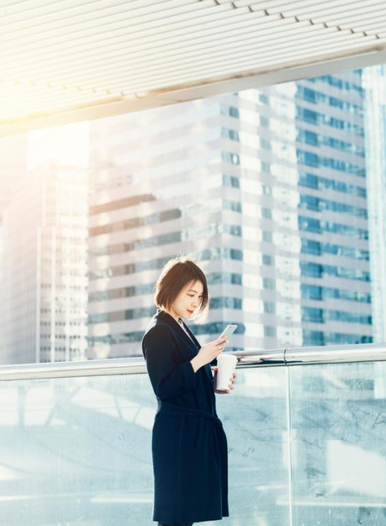 Asian business woman reading phone in city scape