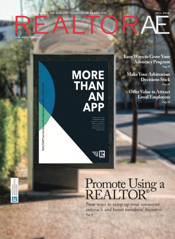 Cover of REALTOR® AE Fall Magazine with the slogo More Than An App on a billboard on a sidewalk