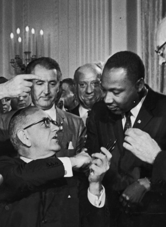 US President Lyndon B. Johnson shakes the hand of Dr. Martin Luther King Jr. at the signing of the Civil Rights Act