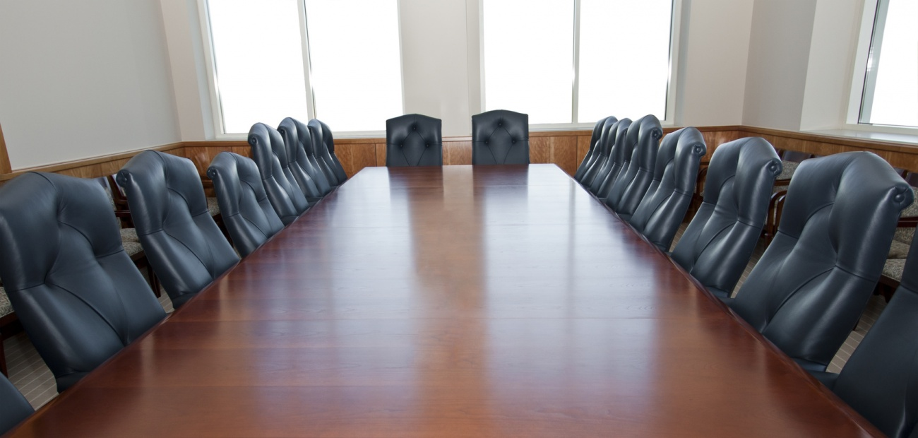 Empty boardroom table and chairs