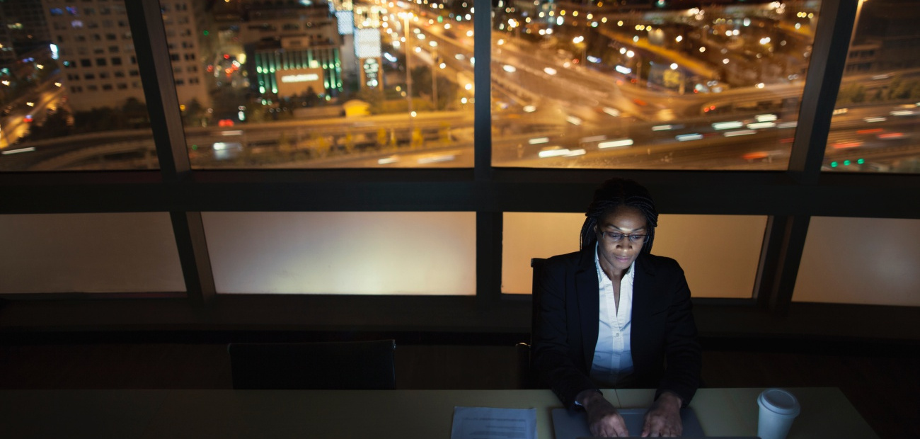 Businesswoman working on laptop at night in office downtown