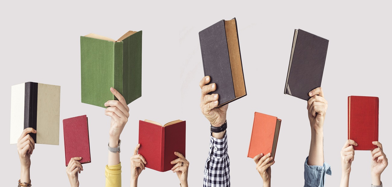 a bunch of hands holding up different colored books