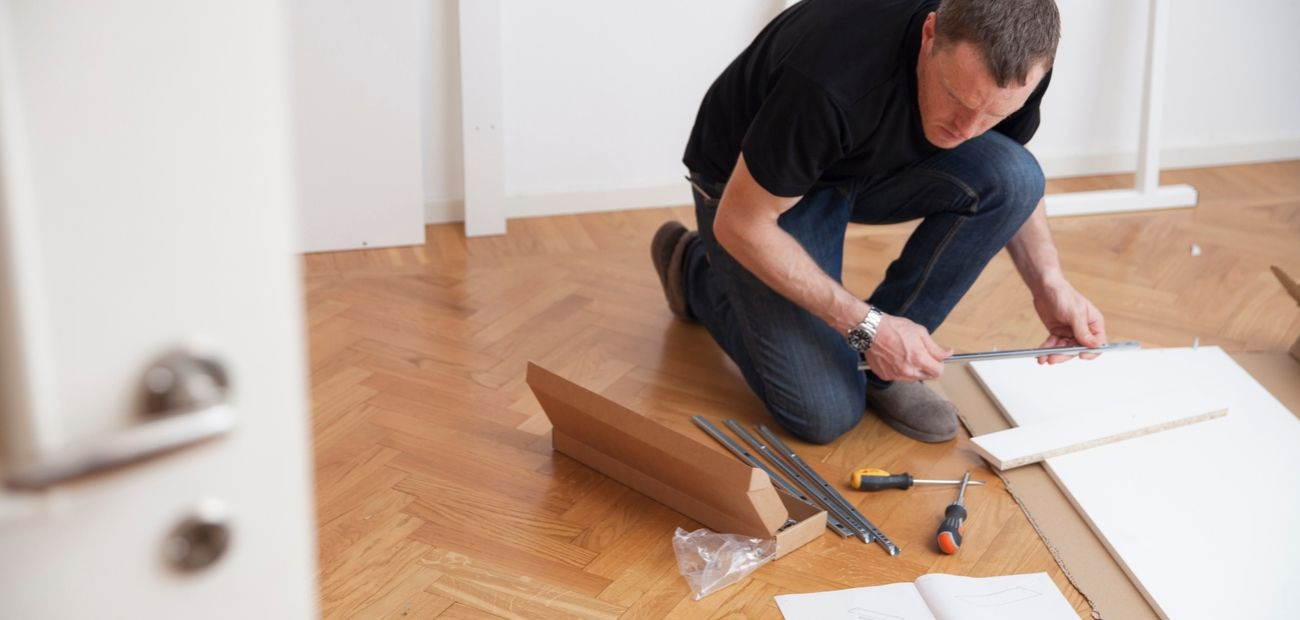 Man kneeling on floor in black shirt and jeans while assembling furniture