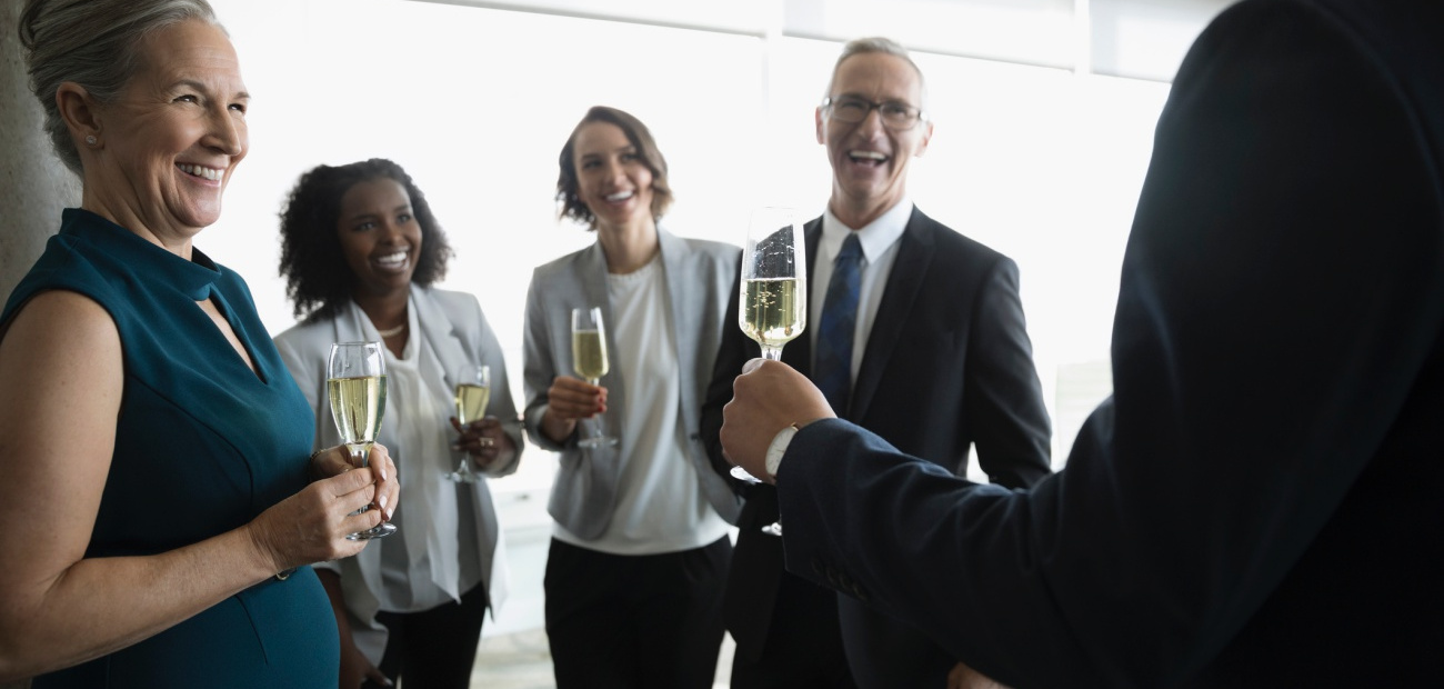 Happy business people celebrating, drinking champagne in conference room
