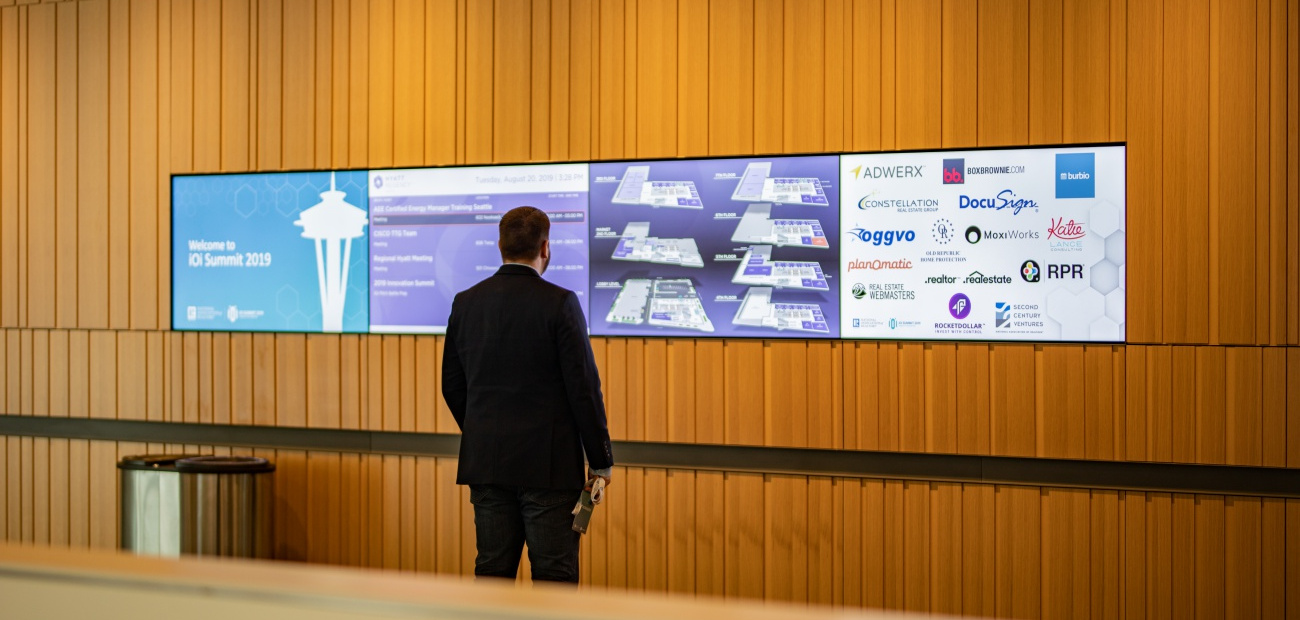 Business man standing in front of 4 screens with sponsor logos and iOi Summit ad