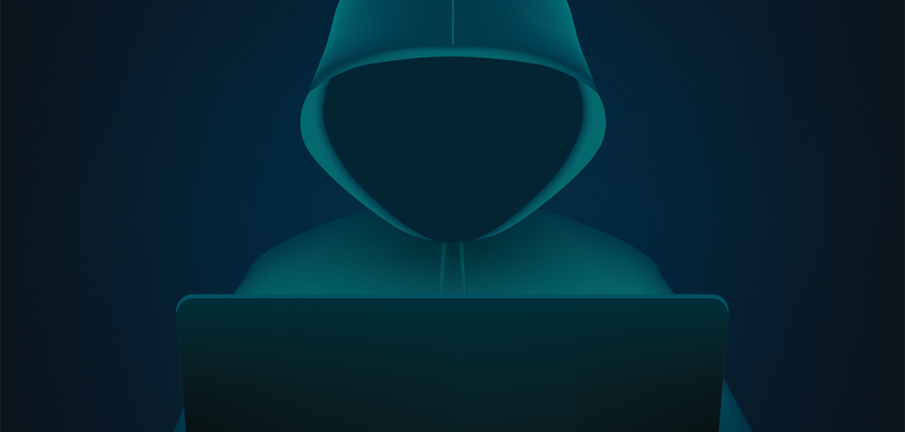 Image of hacker at computer in black and dark green image