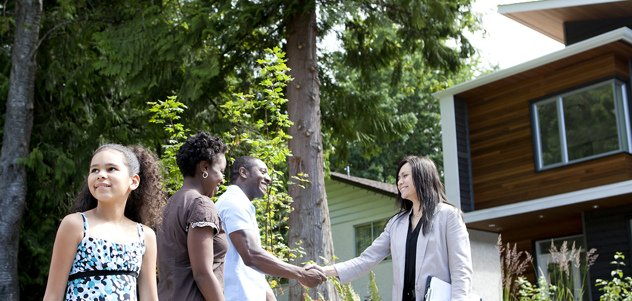 African-American family and real estate agent shaking hands in front of a house